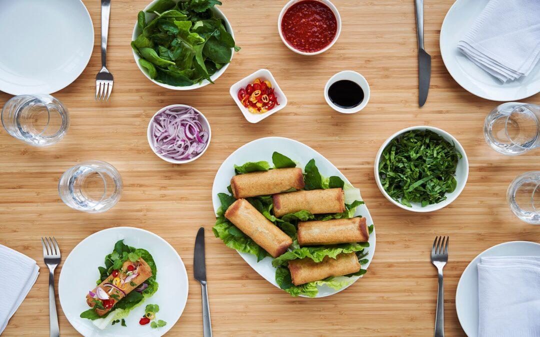 Forårsruller med grøntsager serveret på salatblad med spicy dip