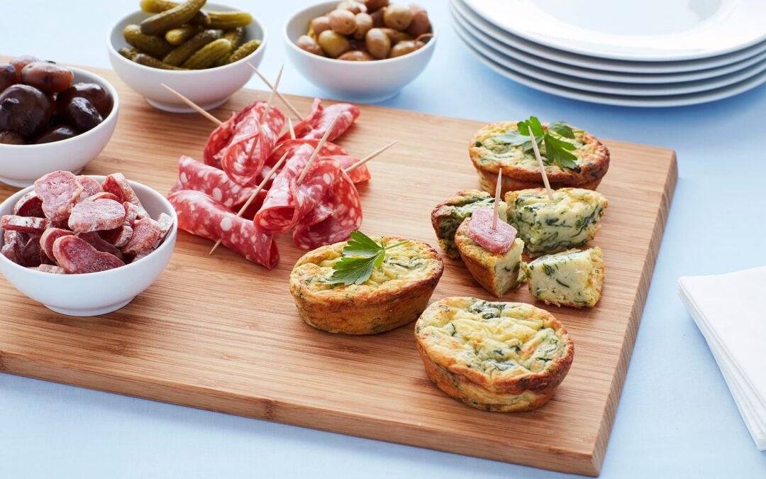 Mini soufflé med spinat og ost anrettet som tapas med charcuteribræt og syltet oliven
